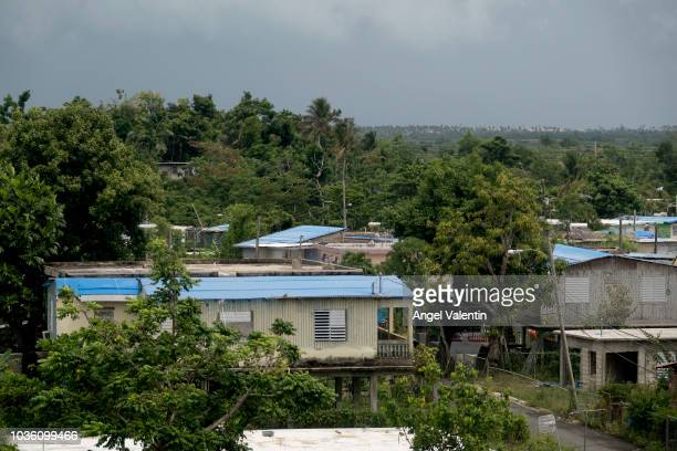 Blue tarps cover houses visible from the expressway in the Northern town of Canovanas on September 19, 2018 in Canóvanas, Puerto Rico. One year after...