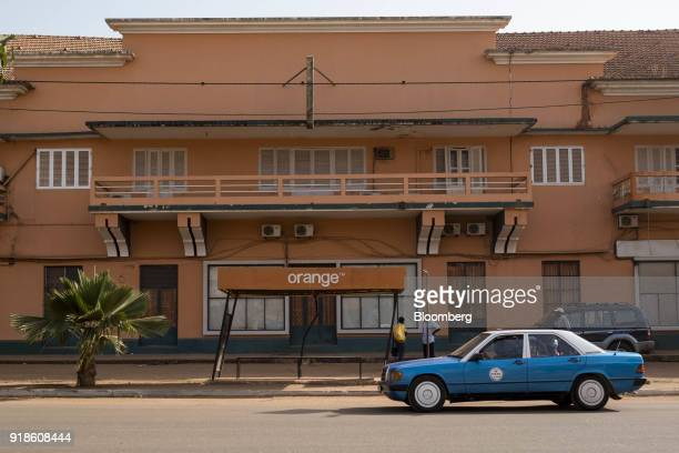 A blue taxi passes by an Orange Bissau SA branded bus stop in Bissau GuineaBissau on Monday Feb 12 2018 The International Monetary Fund said an...