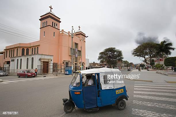Blue three wheel taxi driving past pink church