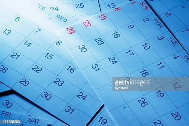 Blue tinted image of calendars with light rays