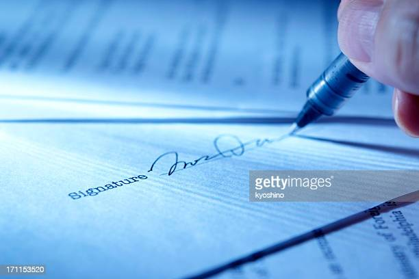 blue tinted image of signing a contract with light rays - permission concept stock pictures, royalty-free photos & images