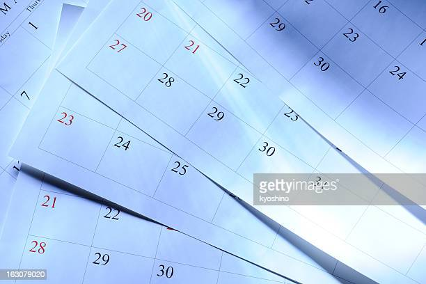 Blue tinted image of some calendars with light rays