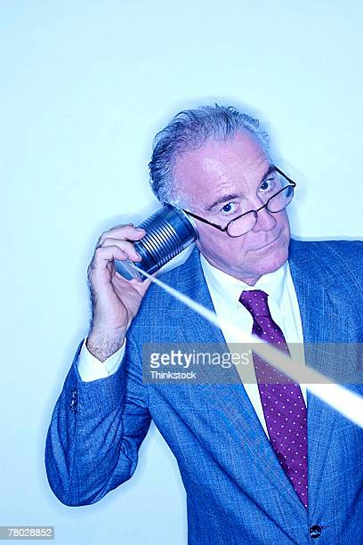 Blue tone of a businessman using a can and rope telephone.
