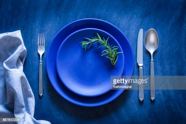 blue toned place setting shot from above on dark background - plate stock photos and pictures