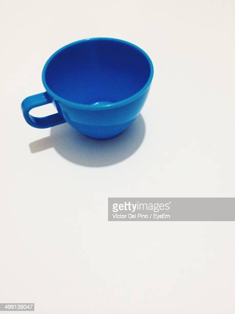 Blue toy tea cup against white background