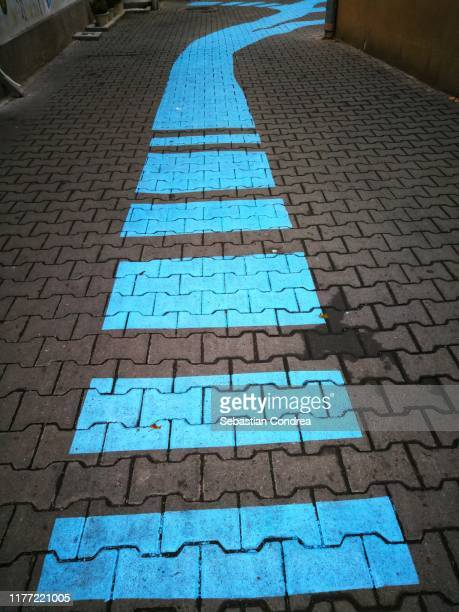 blue traffic arrow signage on the road. - following arrows stock pictures, royalty-free photos & images