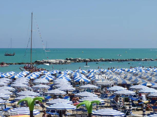blue umbrellas at beach against clear sky - emilia romagna stock photos and pictures