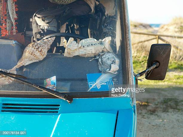 Blue van, newspapers and shells on dashboard, close-up