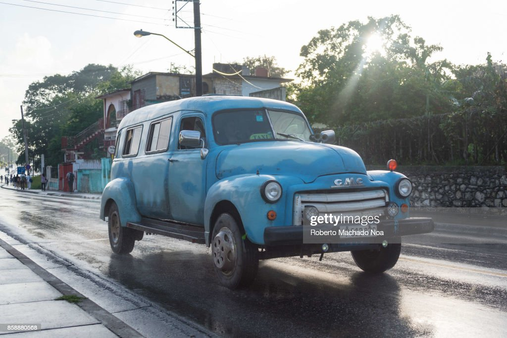 Blue vintage American car running on a wet road and... Pictures ...