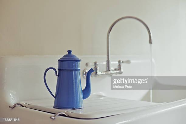 Blue vintage coffee pot next to a running faucet.