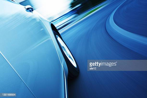 Blue washed motion photo of a car turning a curve in a road