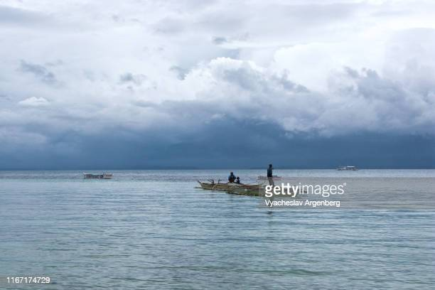 blue water and heavy blue sky, majestic clouds over visayan sea, ethereal atmospheric conditions, philippines - argenberg fotografías e imágenes de stock
