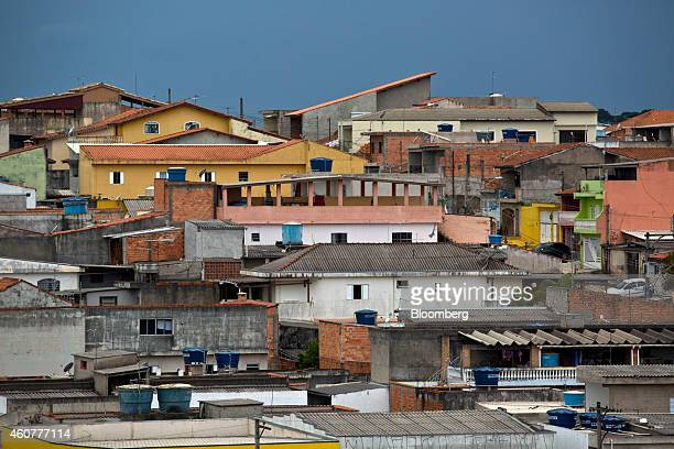 Blue water storage tanks sit on the rooftops of homes near Sao Paulo in Guarulhos Brazil on Friday Dec 12 2014 Sao Paulo residents earning less than...