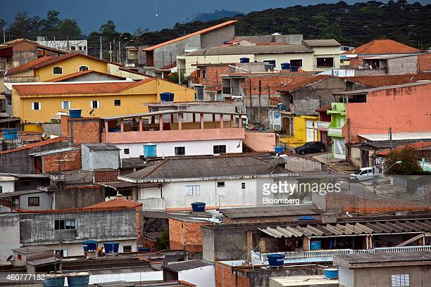 Blue water storage tanks sit on the rooftops of homes near Sao Paulo Guarulhos Brazil on Friday Dec 12 2014 Sao Paulo residents earning less than...