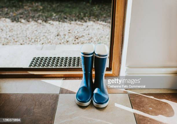 blue welly boots sitting by an open back door. - wellington boot stock pictures, royalty-free photos & images