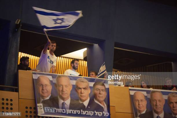 Blue White bloc supporters wave Israeli flags during a rally for Benny Gantz leader of the Blue White party at the Cameri theatre in Tel Aviv Israel...