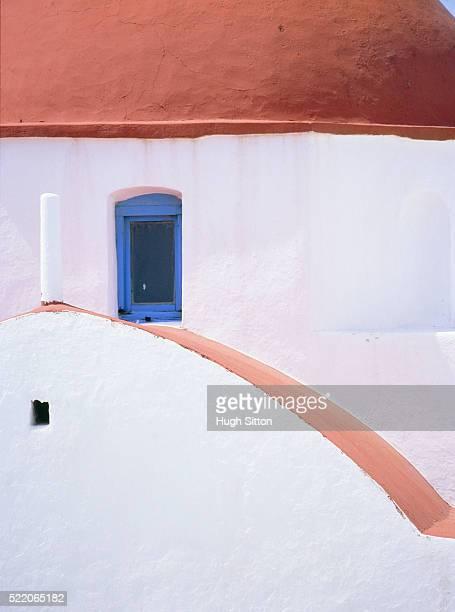 blue window of a white church with red dome on mykonos, greece - hugh sitton fotografías e imágenes de stock