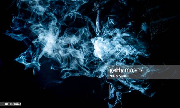 blue wispy smoke on black background - fumo materia foto e immagini stock
