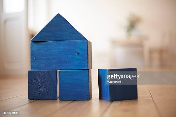 Blue wooden building bricks shaping a house