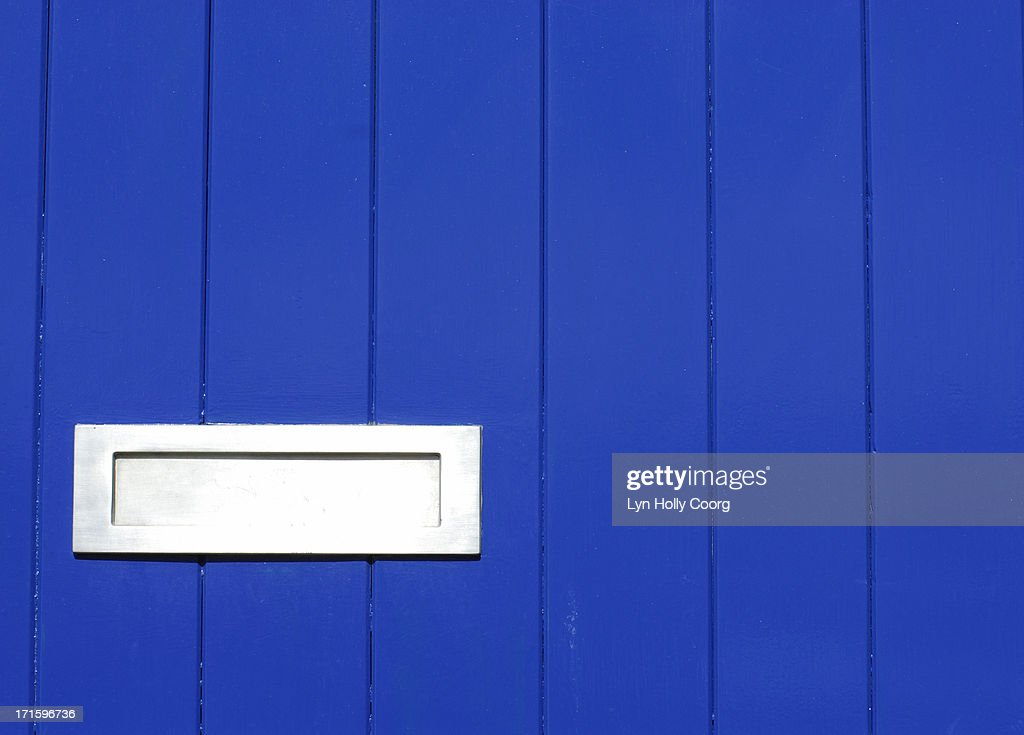 Blue wooden door with silver letterbox : Stock Photo