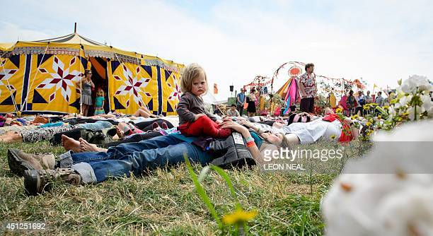Bluebell aged 14 months from Norfolk looks around as her mother takes part in an openair yoga session in the Green Fields as revellers gather ahead...