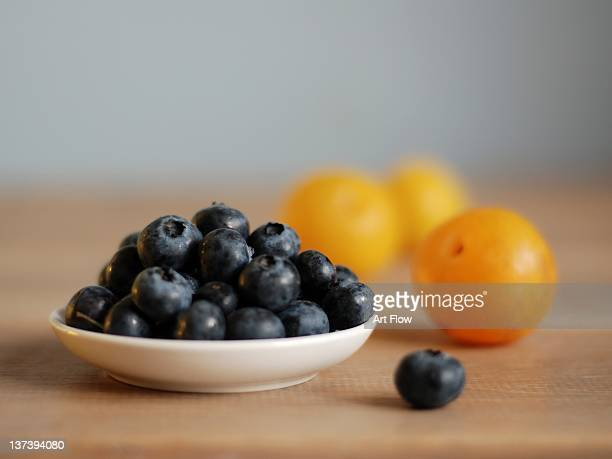 Blueberries and mirabelle plums on table