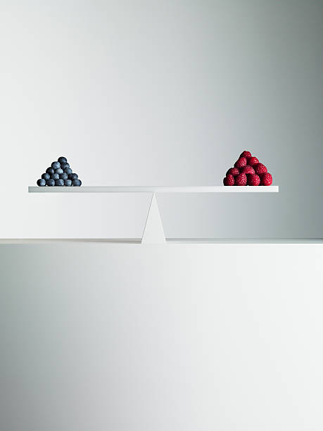 blueberries and strawberries balanced on opposite ends of seesaw - 對稱 個照片及圖片檔