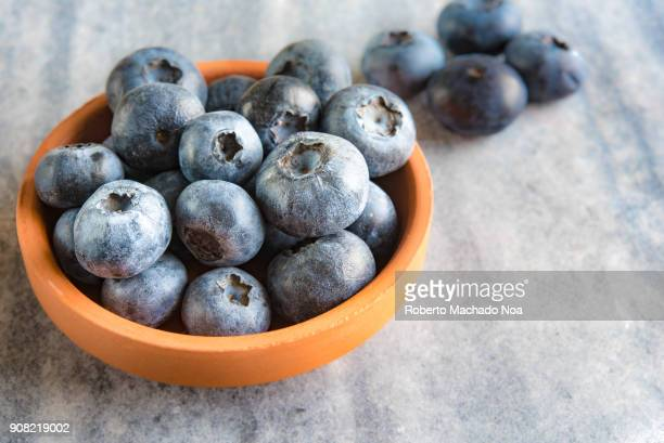 Blueberries fruit is a small clay recipient They are over a marble surface Health benefits of the blueberry include being rich in antioxidants