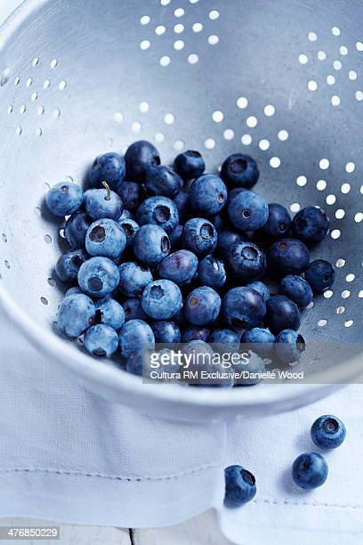 Blueberries in a colander on a white tablecloth
