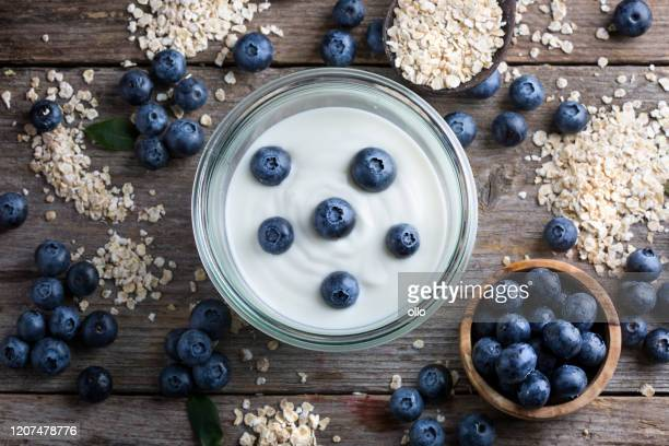 blueberries, oat flakes and yoghurt - yogurt stock pictures, royalty-free photos & images