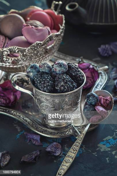Blueberry and BlackBerry berries in silver metal Cup and freshly baked pasta with bokeh of lights...