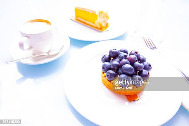 blueberry and lemon cake with cappuccino coffee - high key stockfoto's en -beelden