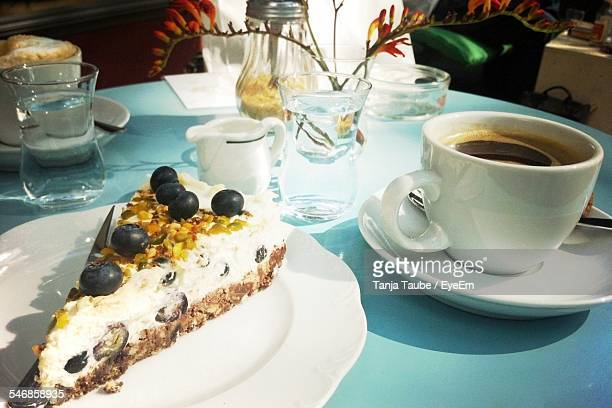 Blueberry Cake Slice And Coffee Cup At Cafe Table