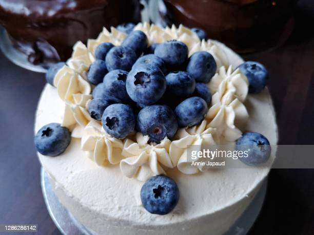 blueberry cake with cream frosting, more cakes in background - cake stock pictures, royalty-free photos & images