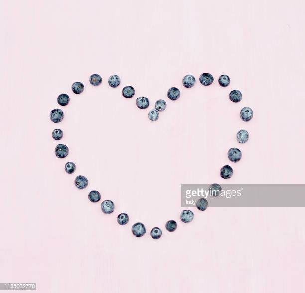blueberry heart on pink background - antioxidant stock pictures, royalty-free photos & images