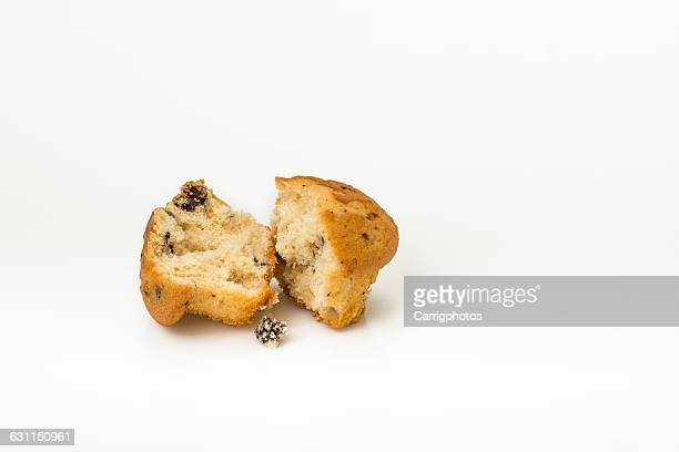 Blueberry muffin torn in half on white background