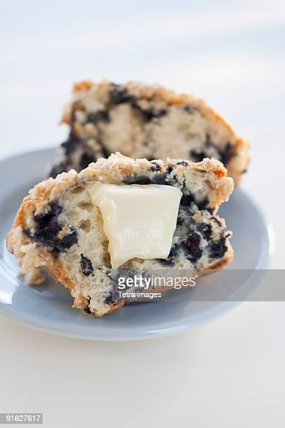 A blueberry muffin with butter