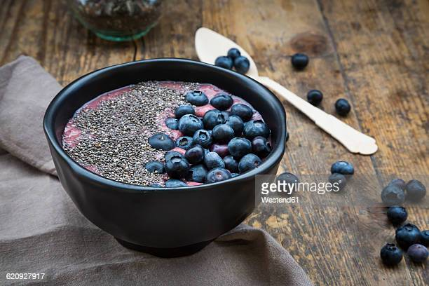 Blueberry smoothie with chia seeds in bowl, fresh blueberries