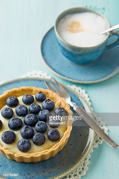blueberry tart with vanilla pudding and cappuccino on table - doily stock photos and pictures