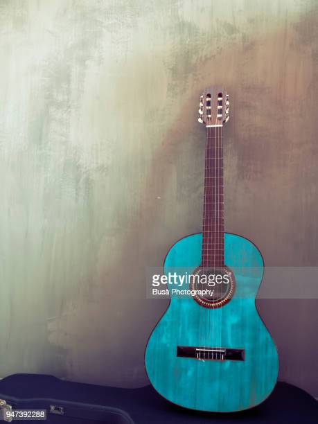 blue-colored classic guitar in a room with a concrete wall - guitar stock pictures, royalty-free photos & images