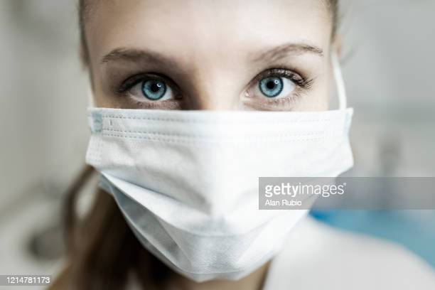 blue-eyed nurse at her workplace wearing a protective mask. - máscara quirúrgica fotografías e imágenes de stock