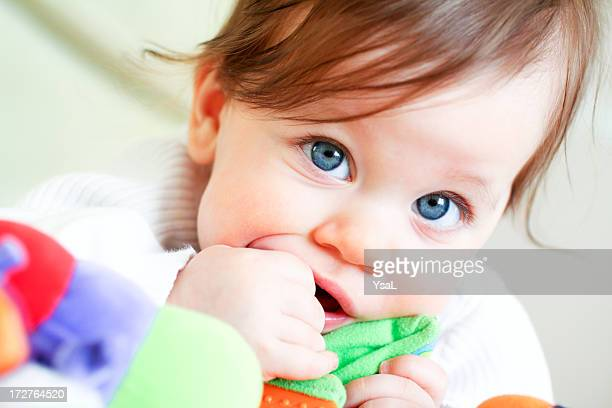 A blue-eyed toddler discovering their toy