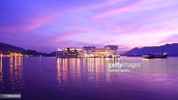 bluehour view of taj lake palace floating on lake pichola - udaipur stock pictures, royalty-free photos & images