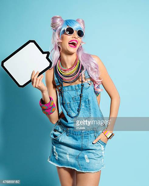 blue-pink hair girl in funky manga outfit holding speech bubble - crazy holiday models stock photos and pictures