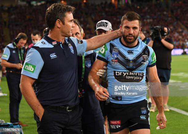 Blues coach Brad Fittler checks on James Tedesco of the Blues after he collided with an opponent during game three of the State of Origin series...