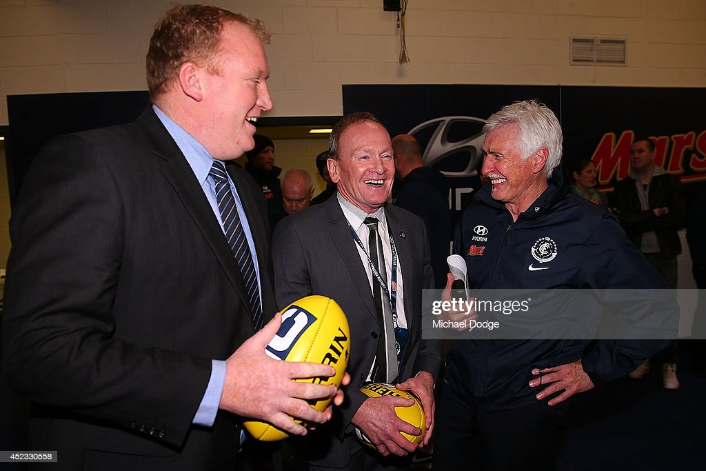 Blues coach Michael Malthouse celebrates the win with former players Lance Witnall (L) and Phil Maylin (C) during the round 18 AFL match between the Carlton Blues and the North Melbourne Kangaroos at Etihad Stadium on July 18, 2014 in Melbourne, Australia.
