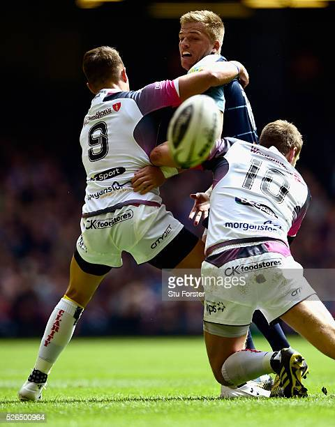 Blues fly half Gareth Anscombe is tackled by Rhys Webb and Dan Biggar of the Ospreys during the Guinness Pro 12 match between Cardiff Blues and...