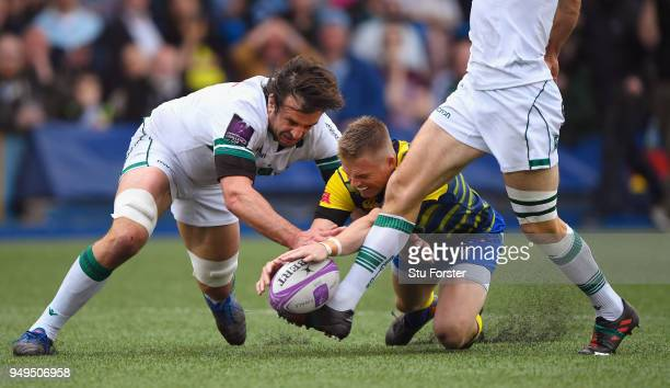 Blues fullback Gareth Anscombe contests a loose ball with Pau forward Julien Pierre as the boot of Conrad Smith waits to intervene to score their...