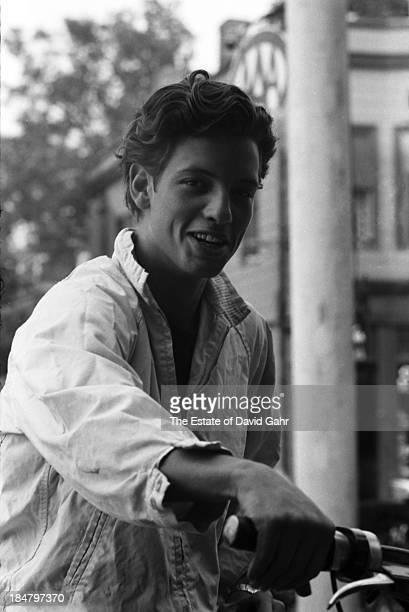 Blues guitarist and singer John Hammond Jr poses for a portrait atop his motorcycle backstage at the Newport Folk Festival in July 1963 in Newport...