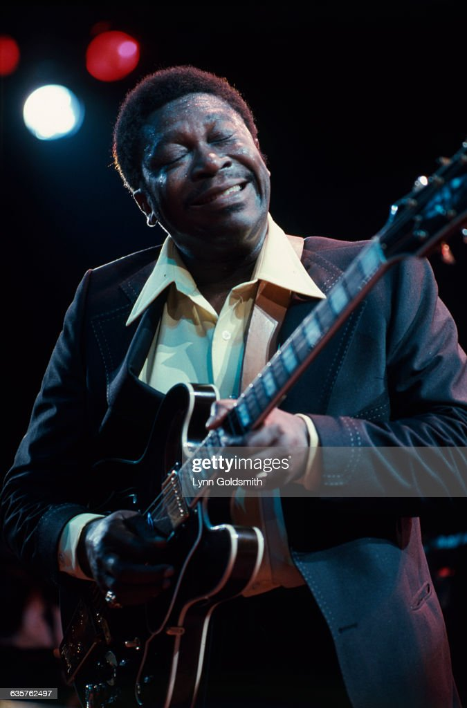Blues guitarist B.B. King on stage performing. He is shown waist-up, with his eyes closed, playing guitar. Photograph, 1981.
